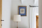 Framed art above a table with a lamp, set off by white walls, beams, and drapery