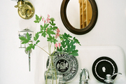 An oval mirror and a brass sconce above a white bathroom sink