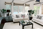 White couches and a black coffee table in a neutral living space