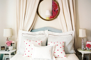 A round gilded mirror hung above a light-blue upholstered headboard