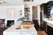A marble kitchen counter top with black pantry cabinets and wooden floors.