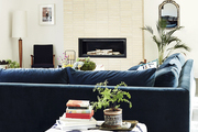 A bone-color brick veneer fireplace set behind a blue velvet sofa and printed ottoman