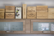 A wine storage area with wooden wine boxes and stemware hidden behind glass and wood shelves.