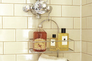 Shower organization with a tiered stainless steel caddy hanging on chrome shower fixture.