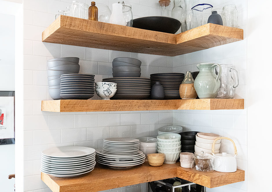 Raw open shelves house a collection of neutral Heath Ceramics in the open kitchen space. Custom Beechwood Floating Shelves.