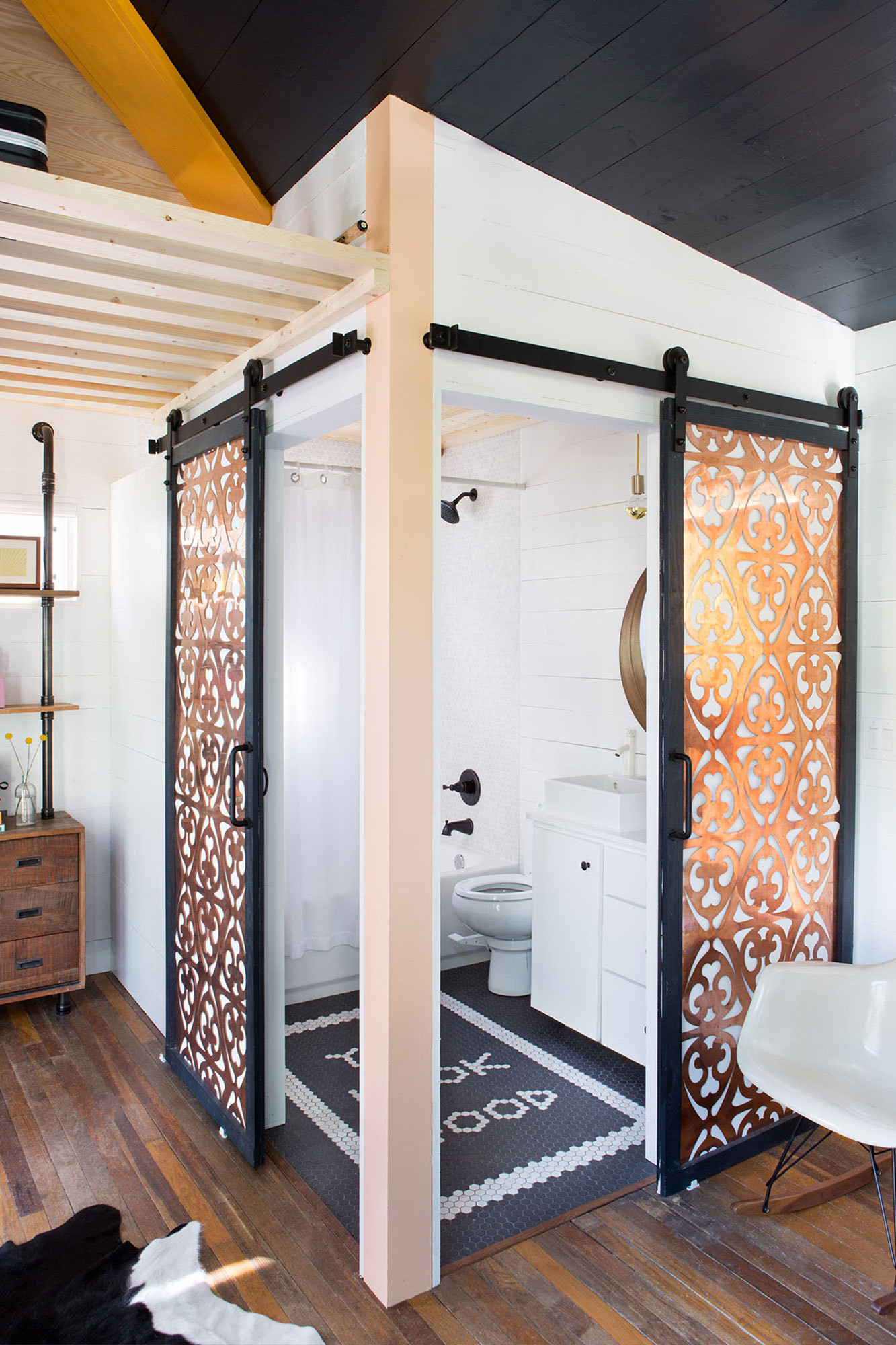 Barn-door track acts as a space saver in place of standard bathroom doors.