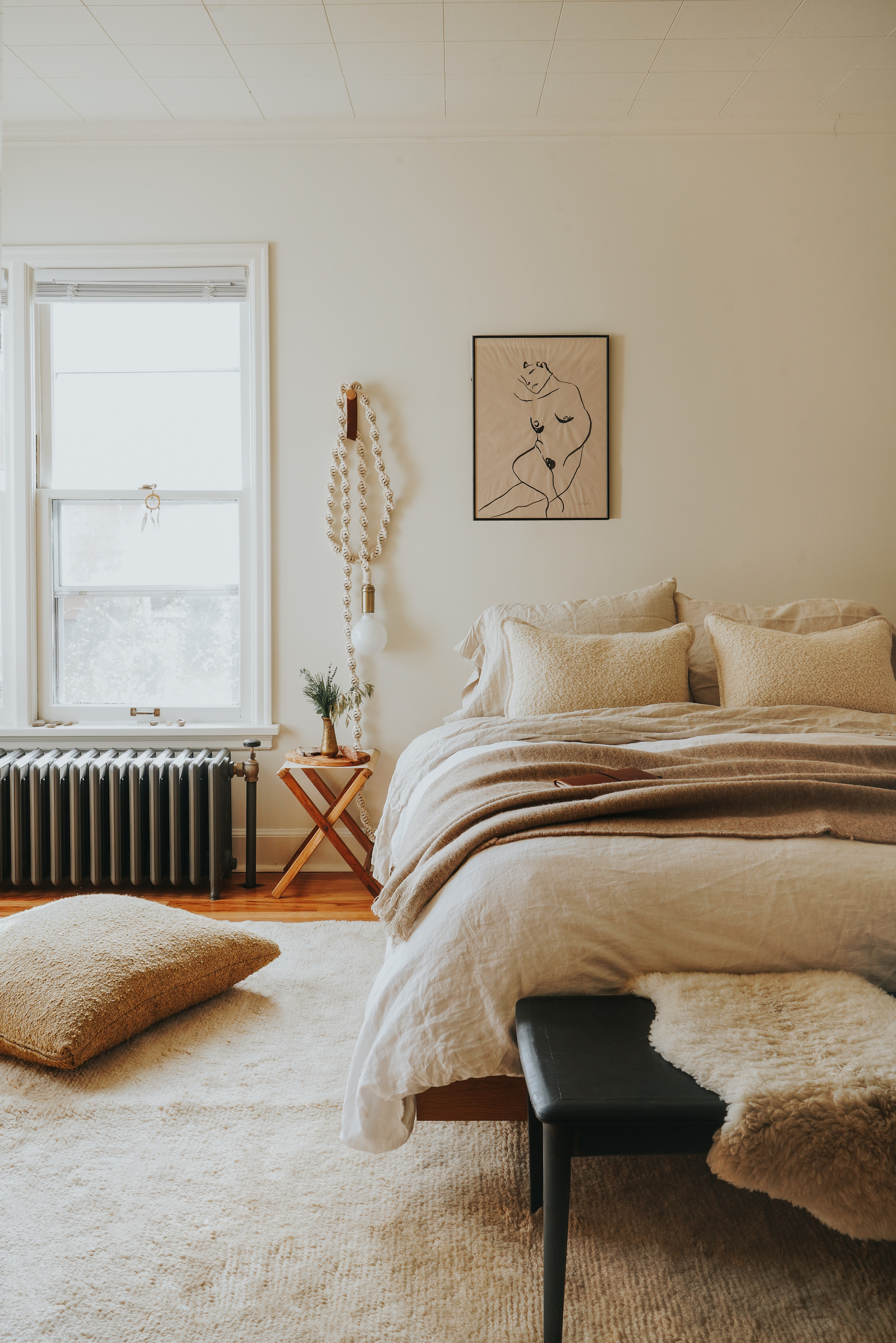 The neutral bedroom leans on rich texture and layers to bring dimension and warmth. Article Bed Frame; Coyuchi Sheets; West Elm Duvet Cover; Pottery Barn Sheepskin Pillow Covers; Windy Chien Rope Light; Elle Luna Artwork; Antique Camp Stool; Vintage Black Bench; Lulu & Georgia Rug; Lulu & Georgia Sheepskin Rug.