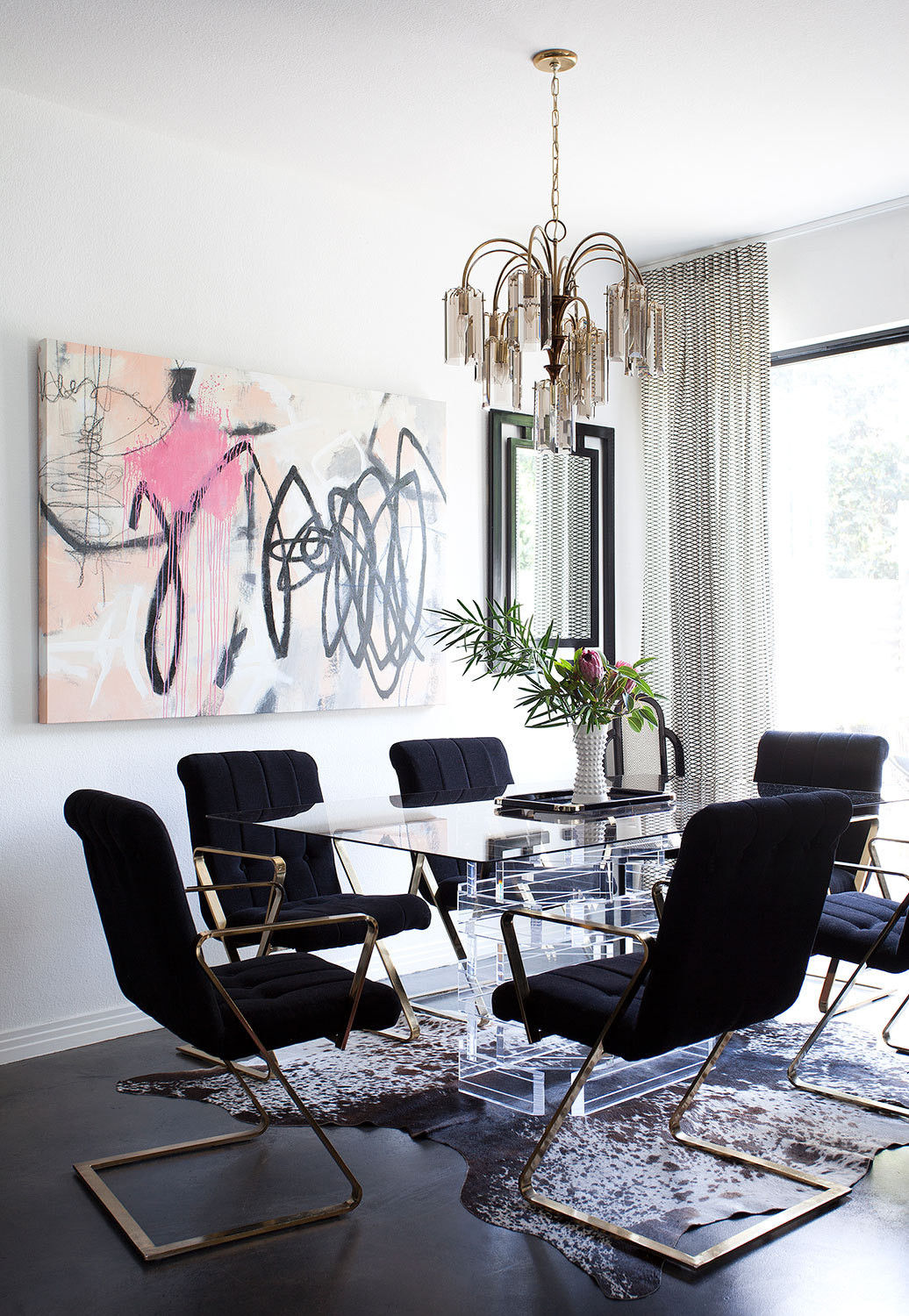 The set of Milo Baughman chairs is one of many standouts in the dining room, along with the graffiti-inspired Elisa Gomez painting and a smoked-glass chandelier found on Craigslist.