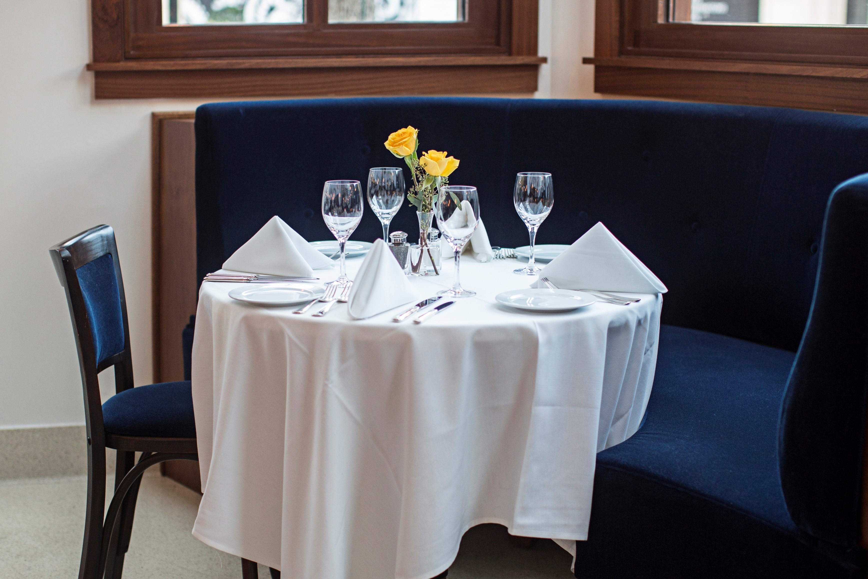 Traditional banquettes covered in rich blue velvet line the perimeter of the modern French bistro.