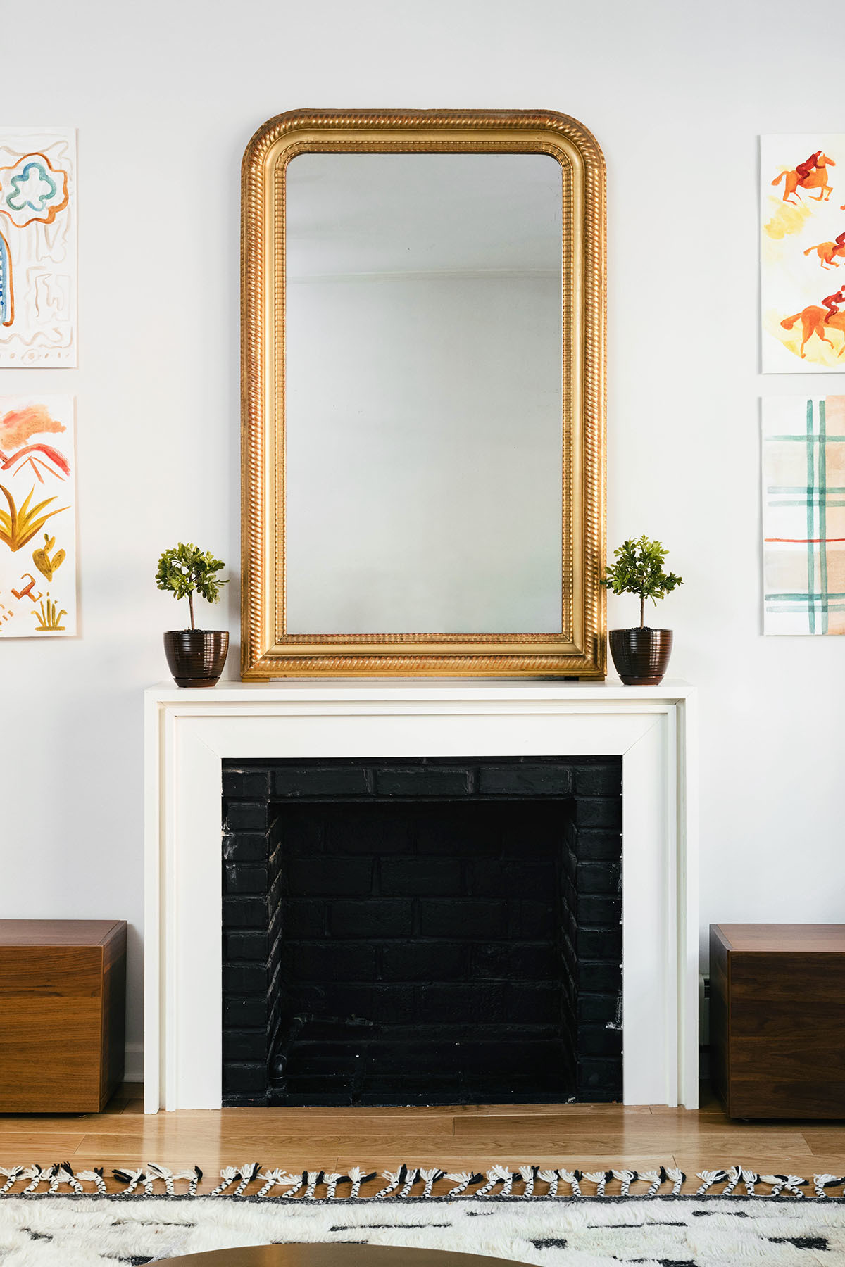 A gilded vintage mirror, sourced via 1stdibs, holds pride of place above the decorative fireplace. Katherine Moffett Artwork | Loloi Rug.