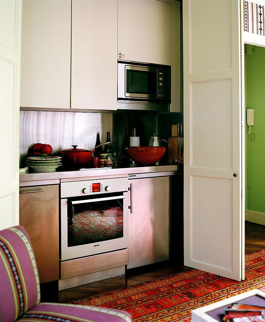 A petite kitchen workspace hides behind two closet-like doors.