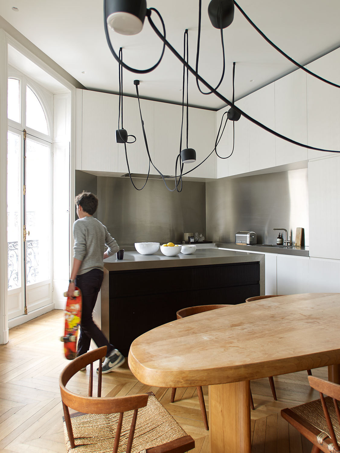 Stainless steel elements and Ronan & Erwan Bouroullec's Aim pendant lamps give the kitchen a futuristic feel.