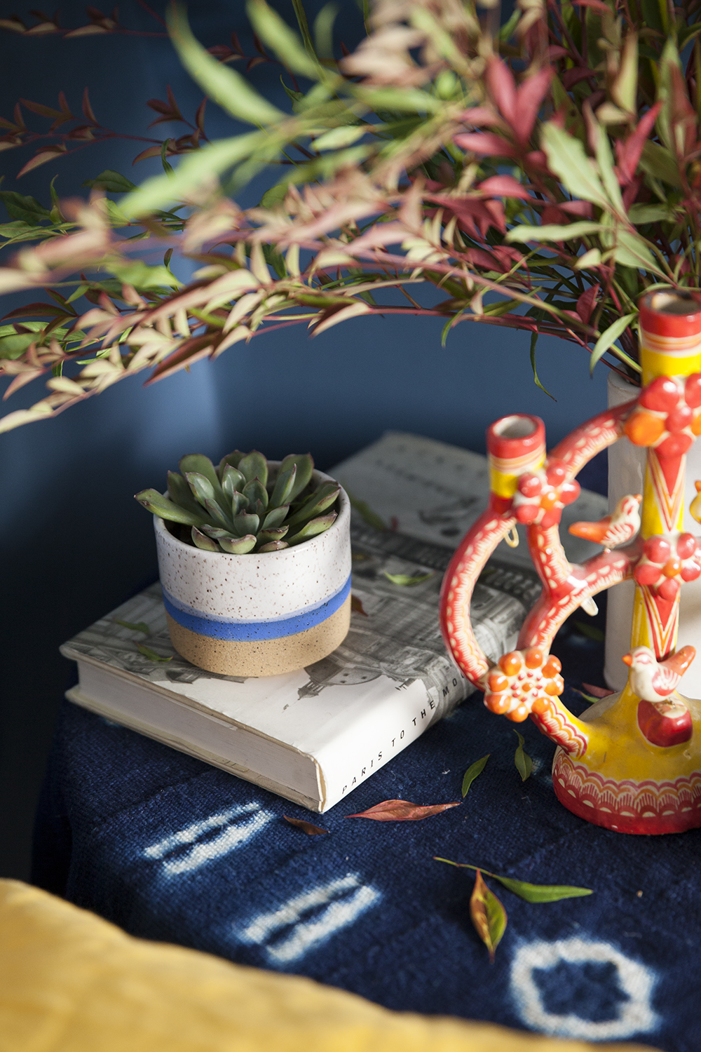 A Ben Medansky ceramic cup is tucked behind an antique tree of life candelabra (above). An original sketch by New York-based artist Saul Lishinsky draws the eye above a pair of staggered antique Chinese stools used in lieu of a nightstand (left).