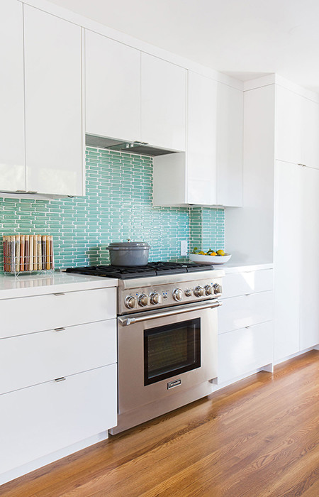 The all-white kitchen begged for a pop of color, so Soria tiled the backsplash in sea-green tiles from Fireclay. The Thermador range is flanked by white Ceasarstone countertops.