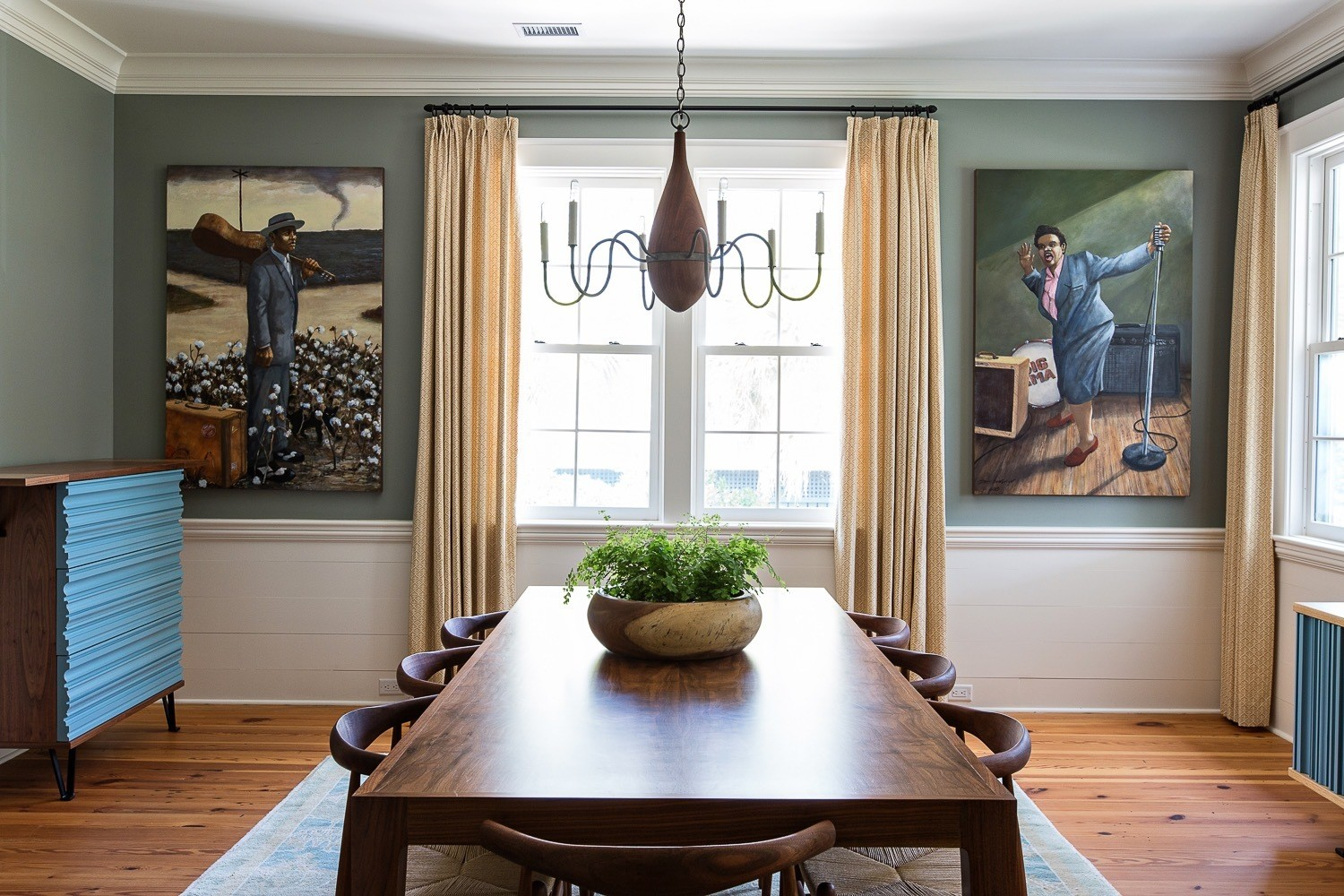 The dining room is another space in the home that combines a mix of artwork that the homeowners have collected throughout the years, custom furnishings, and vintage accessories that help give this room a story of its own. Both paintings are by local Charleston artist David Boatwright and the curtains are by Katie Leede.