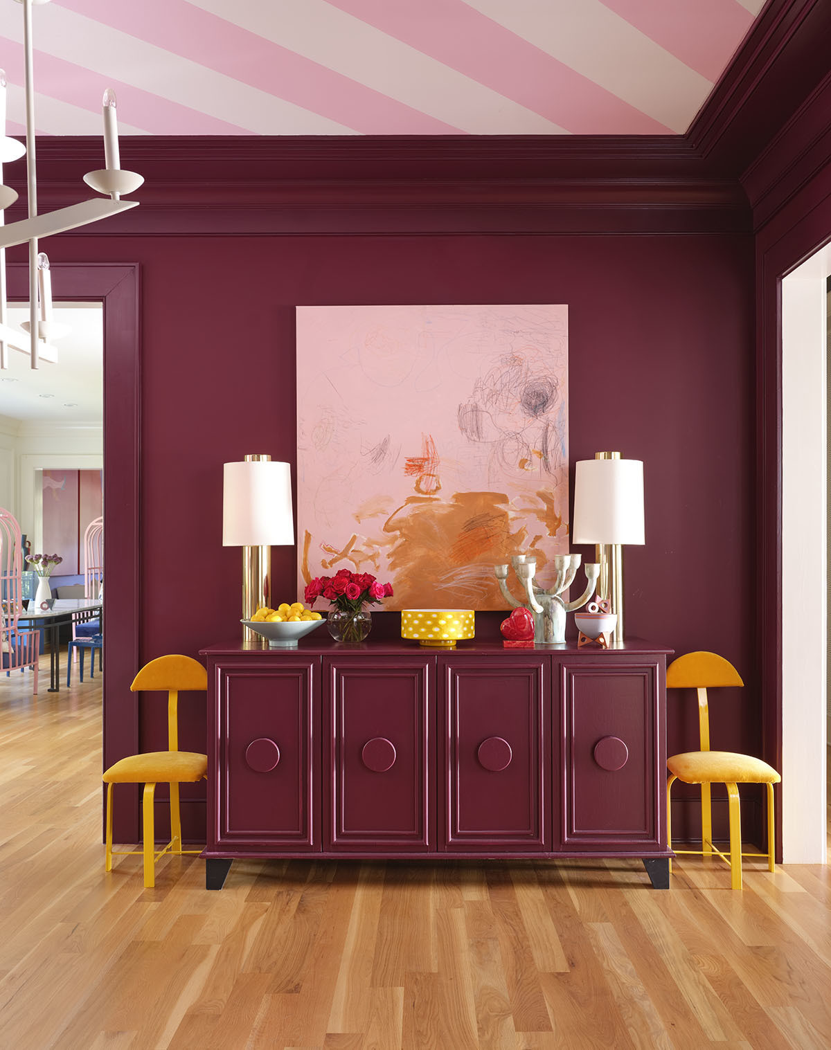 Burgundy, pink, and orange clash in the most spectacular fashion.Benjamin MoorePaint | Custom Side Board | Gillian BryceTable Lamps | VintageAccent Chairs | CustomCeiling Decal | Artwork by Blehm's Children |