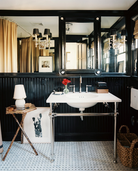The bathroom's unconventional fittings—including a camel-colored shower curtain, vintage rattan tripod table, and dark painted walls—transform a functional space into a design-driven focal point.