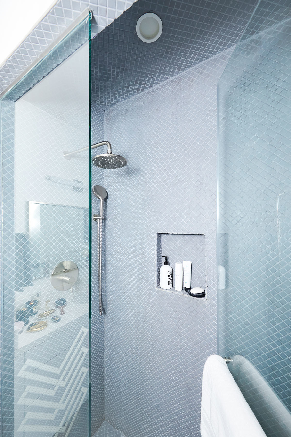 Pale blue tiles in the pared-back bathroom space creates an ultimately soothing vibe.