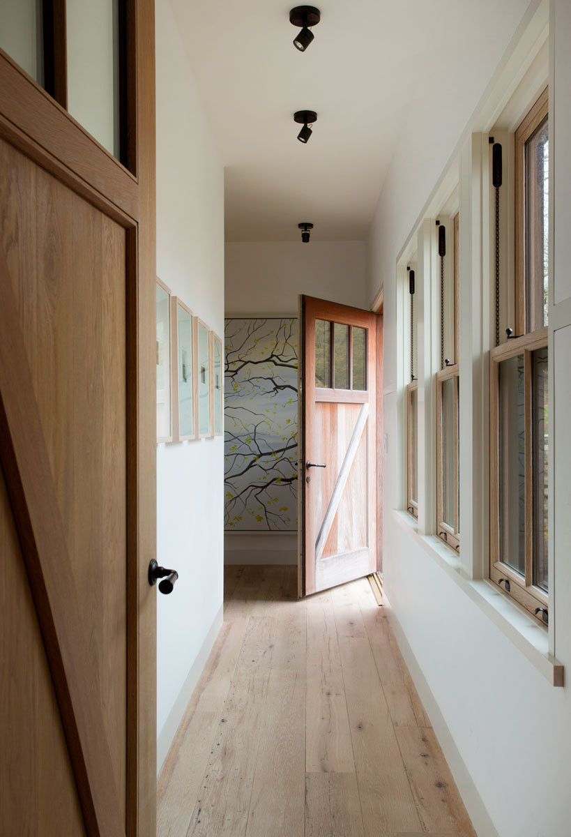 A long hallway leads to a pair of guest rooms, which feature cottage-inspired design details.