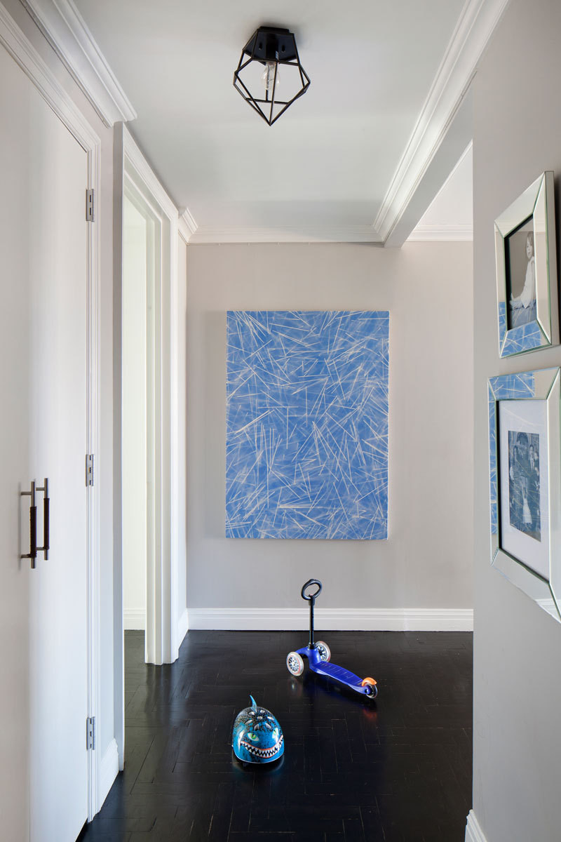 A graphic blue canvas is paired with a ceiling pendant by Young House Love in the entry.