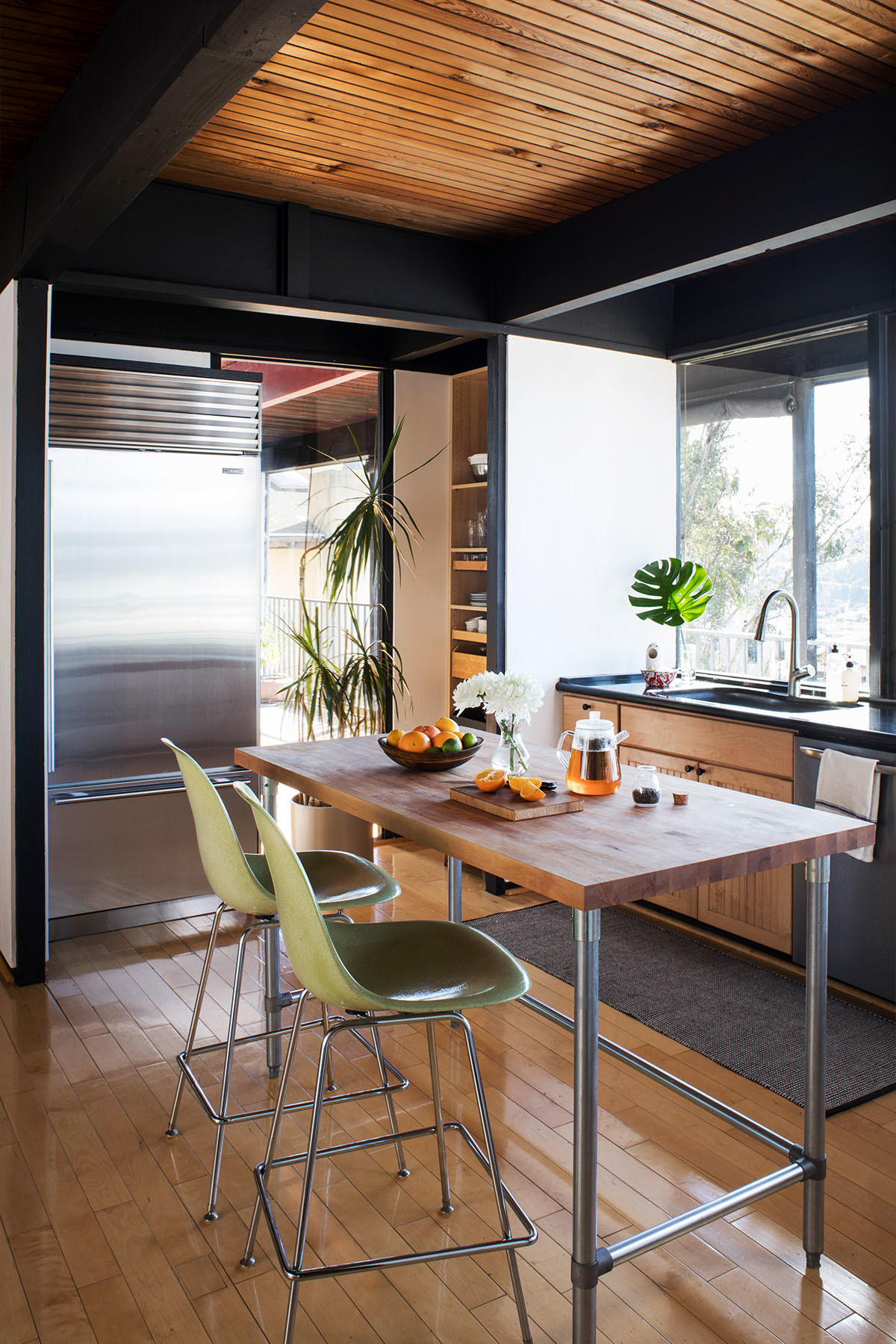 The duo embrace a clean-lined, mid-century aesthetic in the kitchen space, complete with Modernica's fiberglass counter stools and treetop views. John Boos Kitchen Island | Overstock Runner | Sub-Zero, Gaggenau Appliances | Miles Gracey Chopping Board.