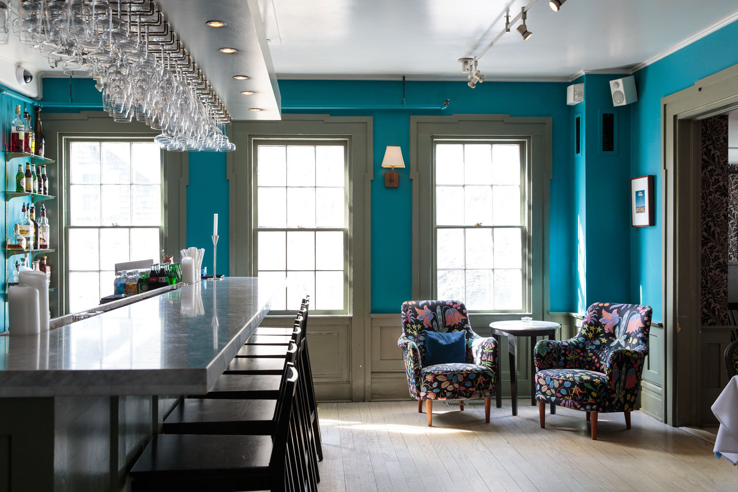 Walls in Benjamin Moore's Wilmington Spruce create a lively backdrop in the Living Room restaurant's bar.