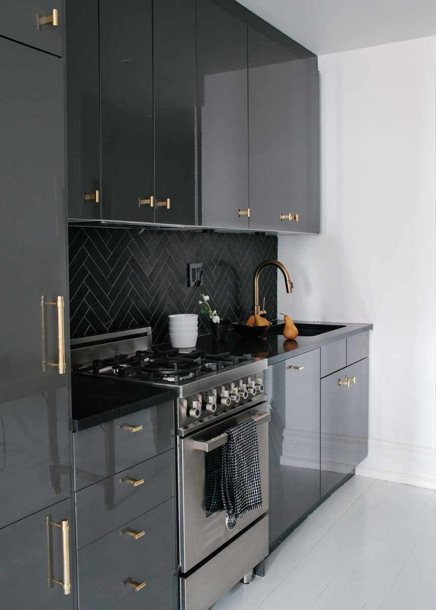 The glossy Ikea cabinetry is accented by bronze hardware and a honed-marble herringbone backsplash.