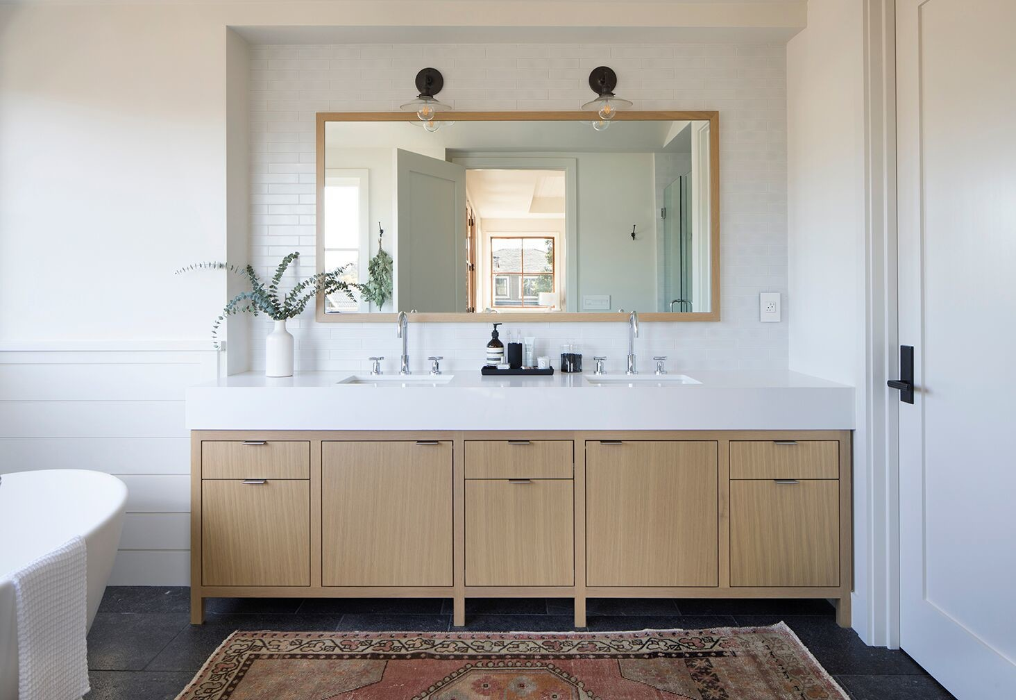 The master bath also features stunning light wood cabinetry and a perfect, warm area rug.