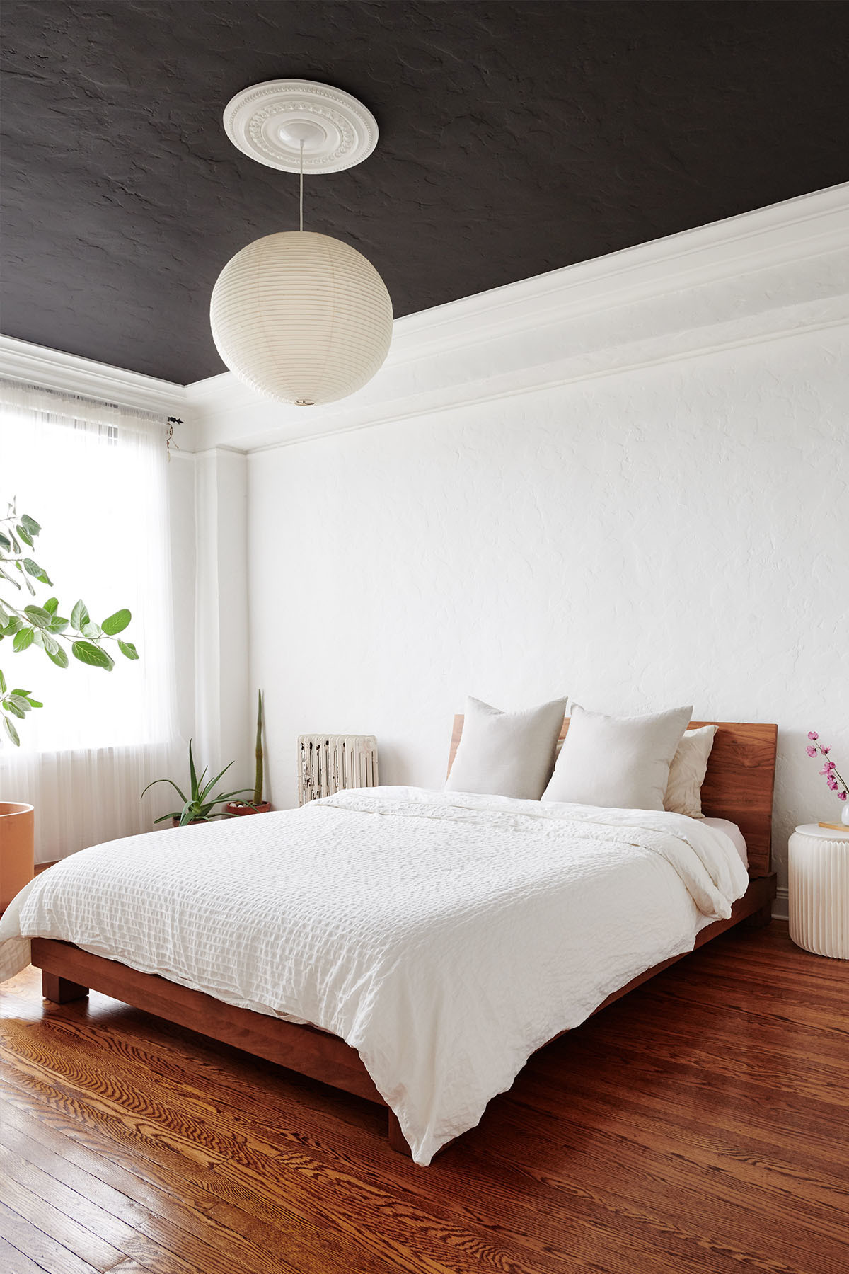 The couple opt for a dark gray ceiling — reminiscent of the night sky — to bring a point of difference to the calming and serene master bedroom space. Benjamin Moore Paint | IKEA Drapes | Millwork Ceiling Medallion | Akari Noguchi Pendant Light | CB2 Bed | IKEA Duvet Cover | Hawkins New York Bedding | Flora Grubb Planters | Amazon Side Table | Heath Ceramics Bud Vase.