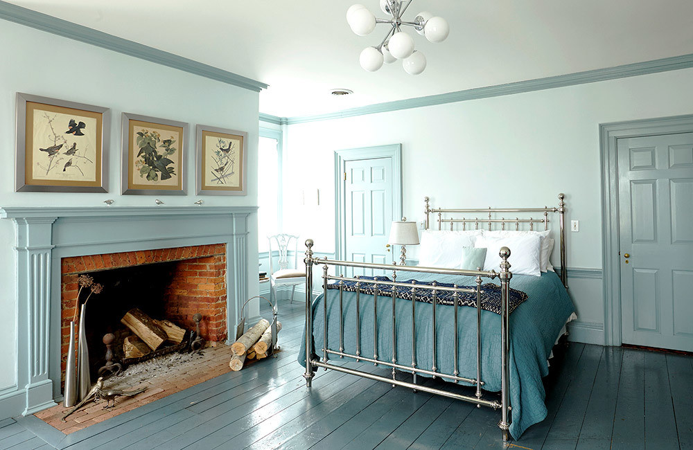 "The master bedroom is decorated in shades of blue, creating a cerulean glow when the sunlight comes in from the east. ""The floor was painted that color when we moved in,"" explains Ridge. ""I wanted to do something different, something cooling so I don't wake up too fast."""