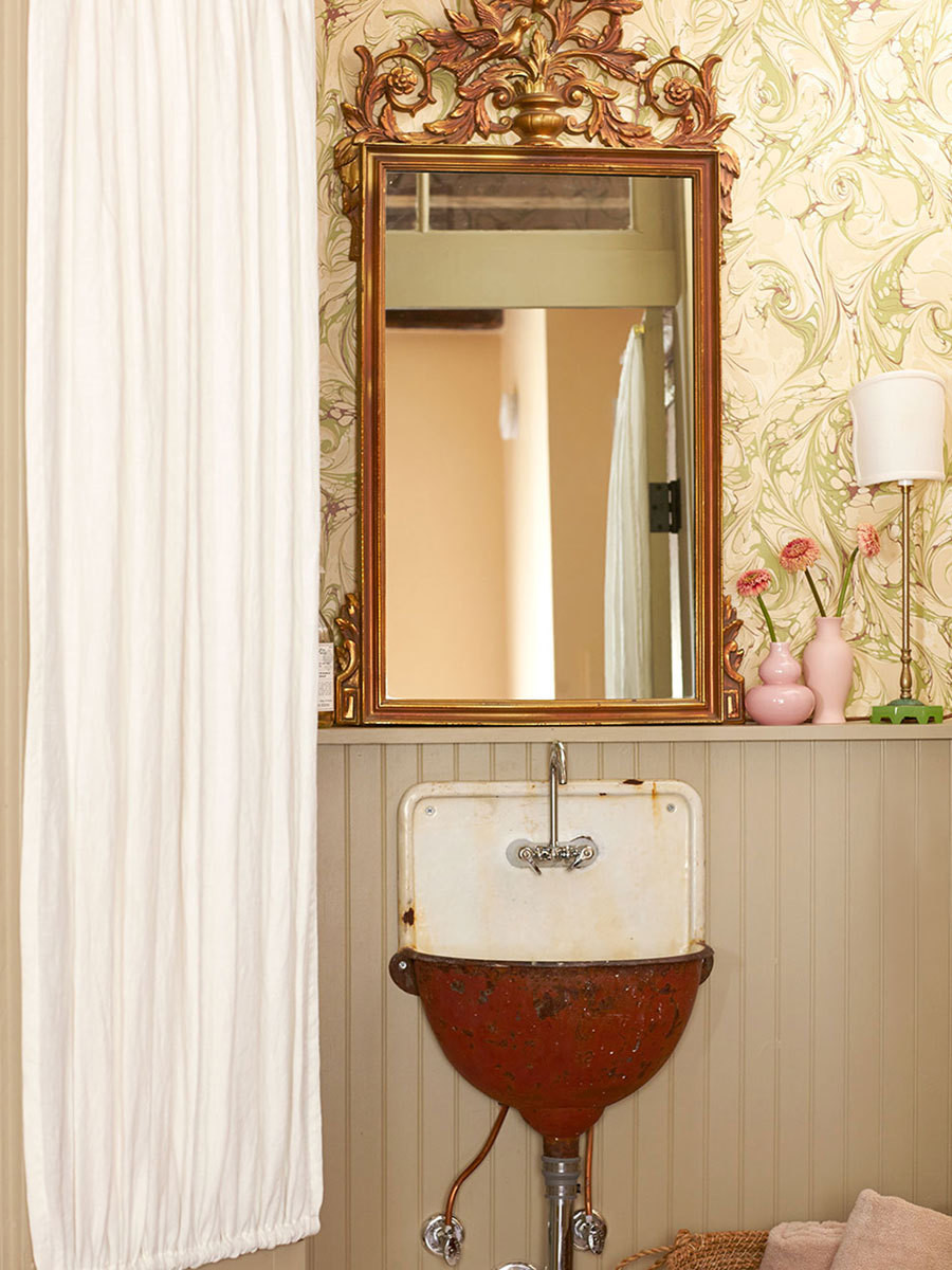 The guest bath's antique sink and gilded mirror.