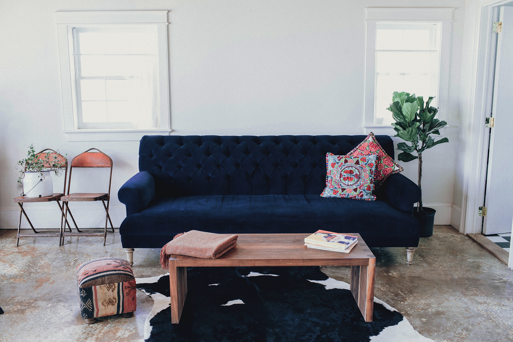The main living space is anchored by a beloved deep blue velvet Chesterfield from ABC Carpet & Home, alongside a pair of vintage accent chairs from Pickren's grandmother. The white bucket atop the seat was salvaged from the original property; And the oak coffee table is a creation of Warner's.