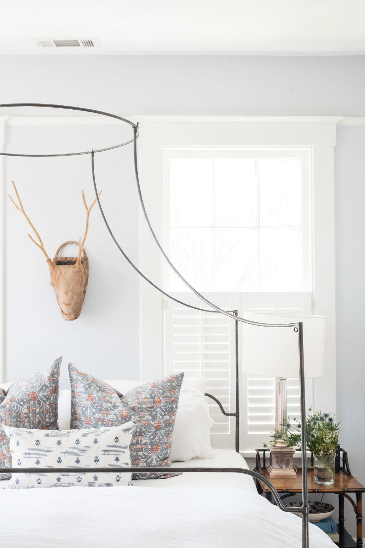 Eichholz opted for a contemporary metal bed frame, from Anthropologie, to avoid obstructing the view from the couple's bedroom window. Sandfly Market Place Decorative Antlers | Zak and Fox Assorted Pillows | One Kings Lane Bedding | Memoky Side Tables | Circa Lamp.