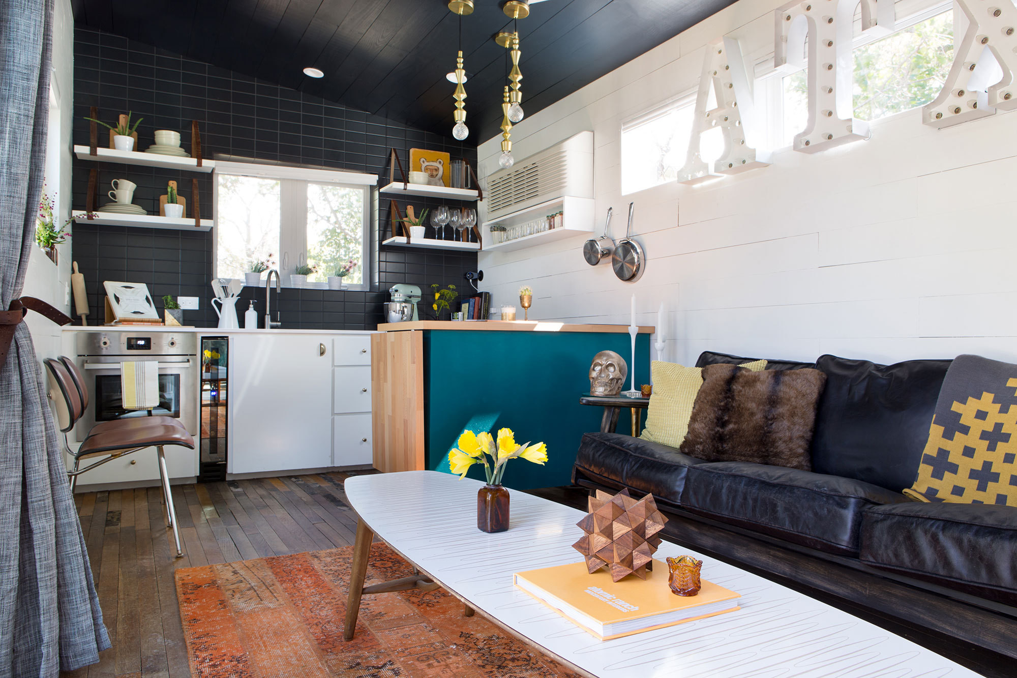 A compact yet efficient kitchen and living area comprises one of two connected trailers in Kim Lewis's design.