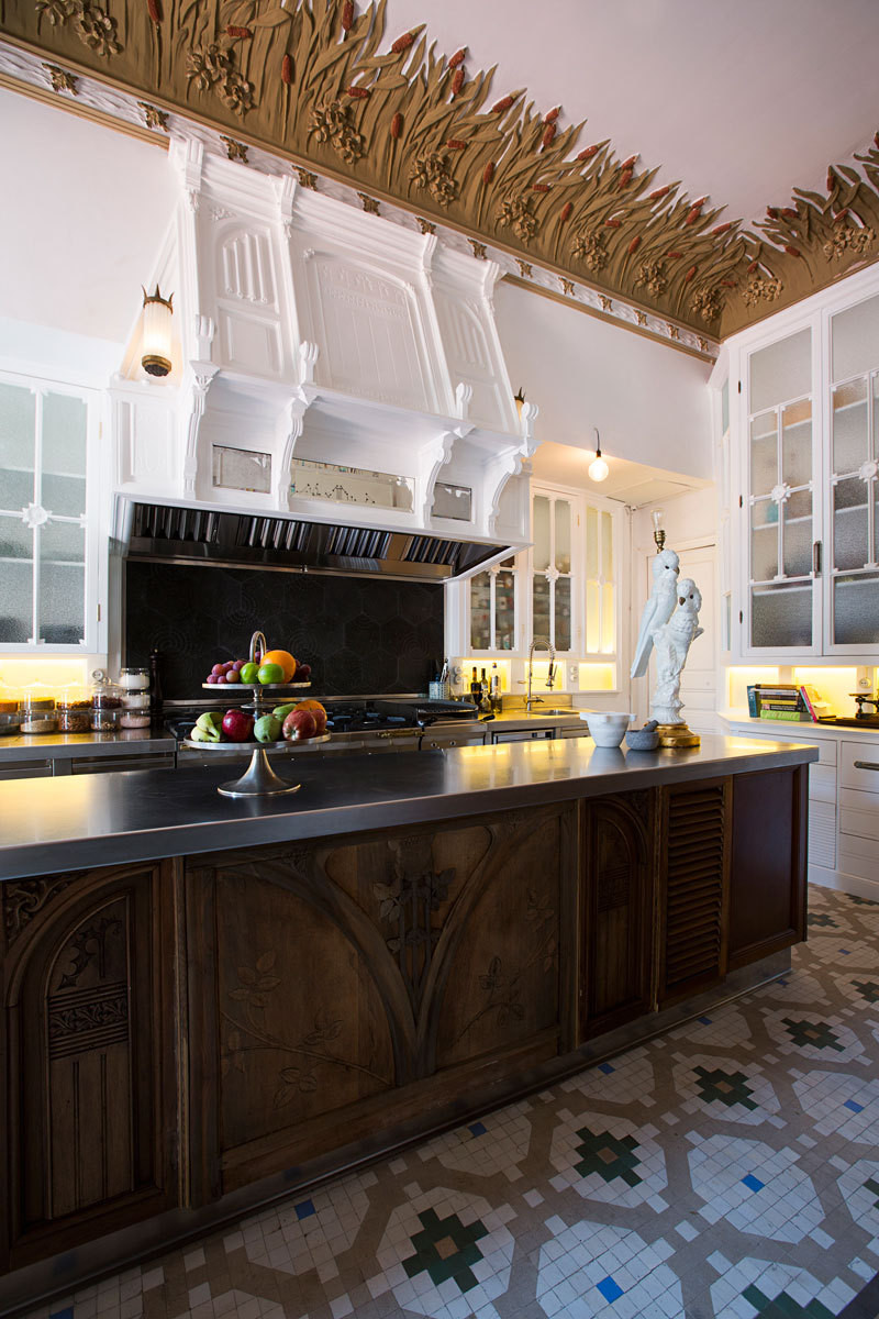 The kitchen island is surrounded in carved wood panels from the Art Nouveau era.