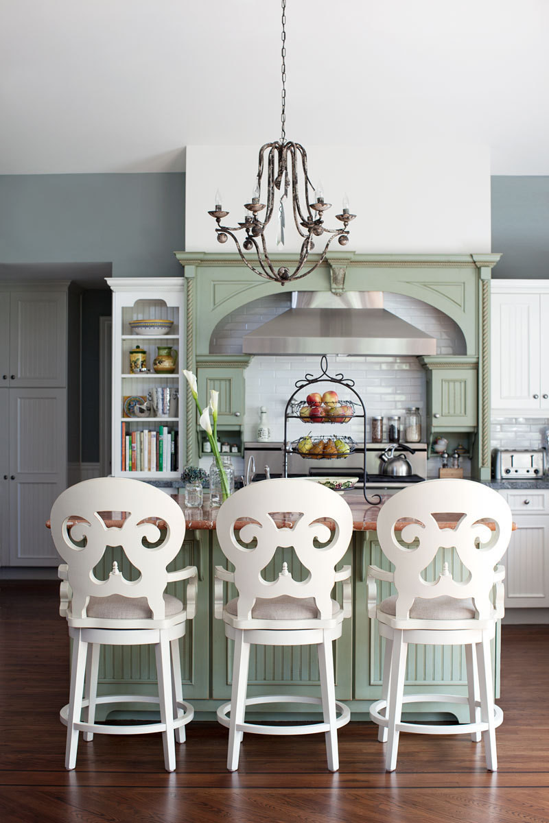 A trio of Jordan Swivel Counter Stools in ivory turns the kitchen island into a comfortable eating area.