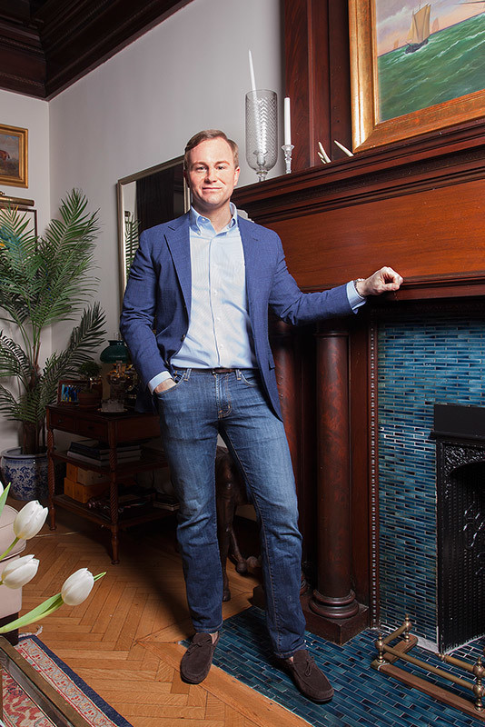 Scott Francis in front of his charming wood-burning fireplace in his apartment in New York City's Gramercy Park.