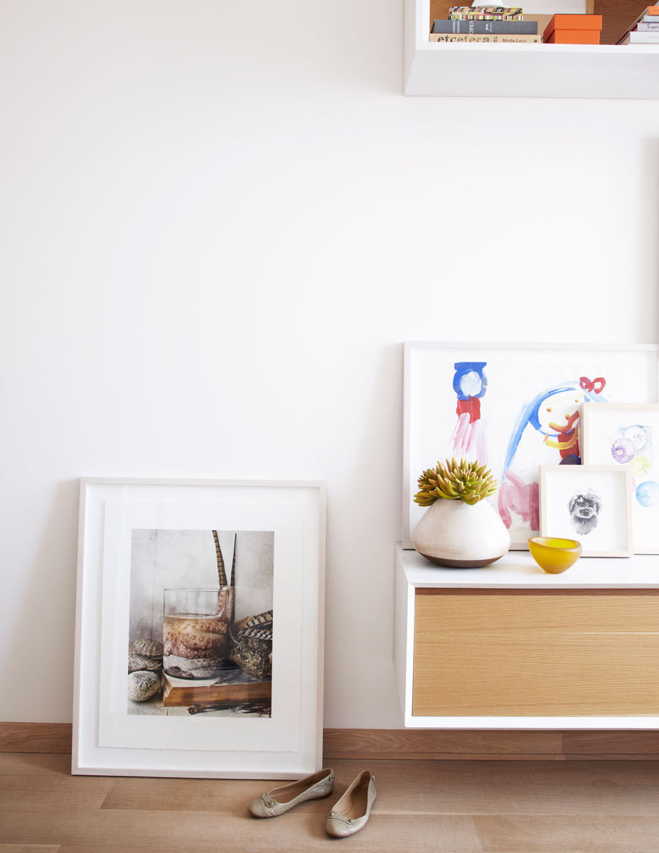 Floating storage and simply framed artworks keep the apartment feeling airy.