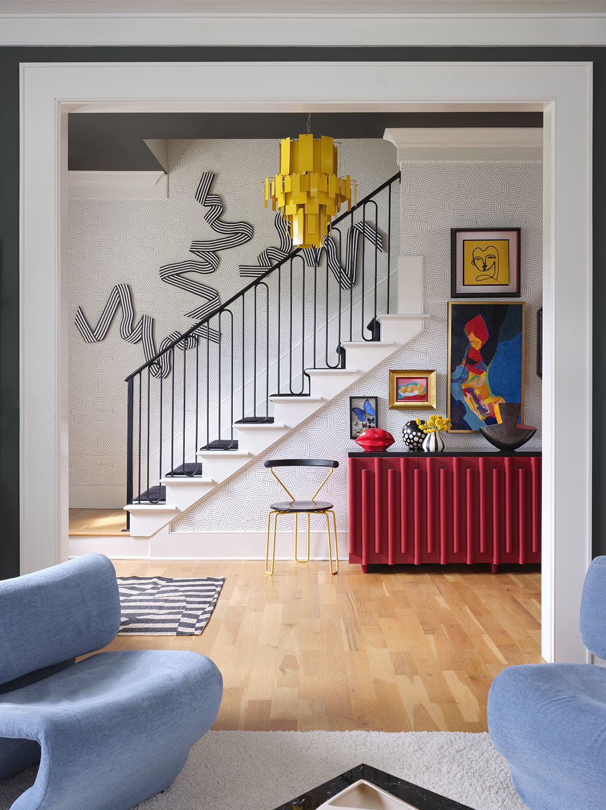 The entryway really showcases the Alice in Wonderland effect with its magical fusion of large-scale art, graphic patterns, and playful color combinations. Custom Chris Lund Cabinet | Custom Yellow Chandelier |Angela Chrusciaki Blehm wall art | Vintage Accent Chair | Vintage Vase |Missoni for Stark Runner |