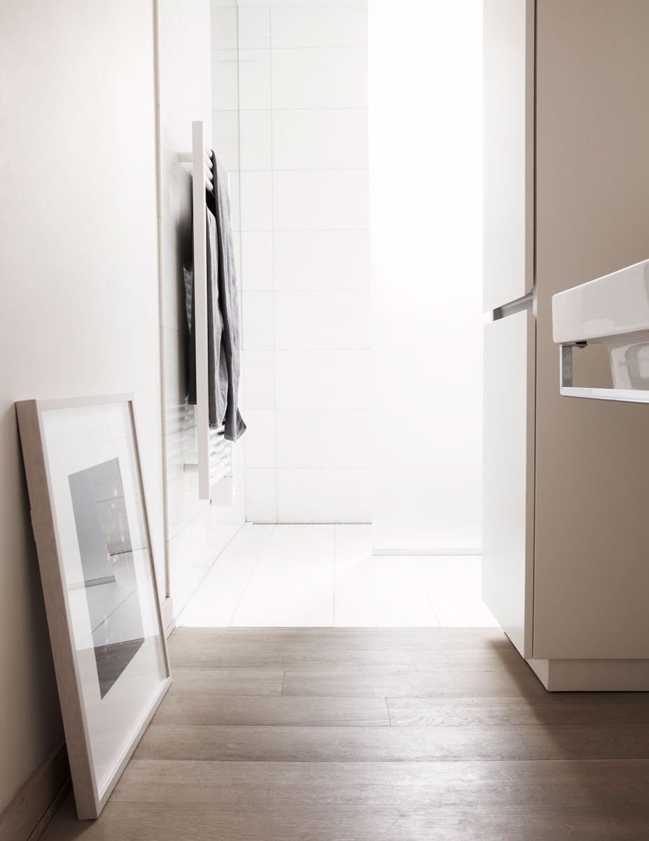 The all-white bath retains a minimal aesthetic thanks to hidden storage.