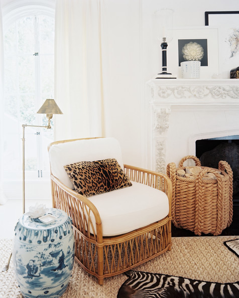 Near the ornate fireplace, a rattan chair is punctuated with a leopard-print throw pillow and a classic blue-and-white garden stool. A thick sisal floor covering is layered with an accent rug in black-and-white zebra.