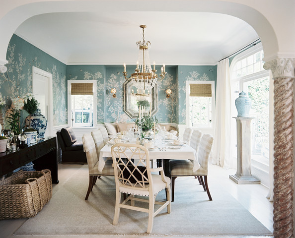 A powder-blue chinoiserie wallpaper envelopes the home's formal dining room, where tan-and-white gingham-upholstered chairs surround a linen-covered dining table.