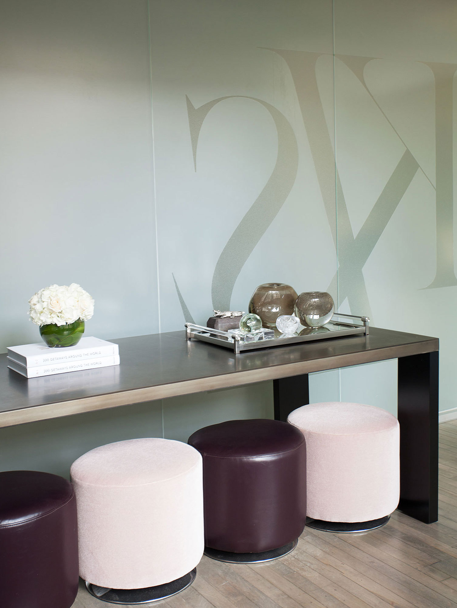Pink and purple stools, custom-made by Fuller, stand at the ready beneath a long table.