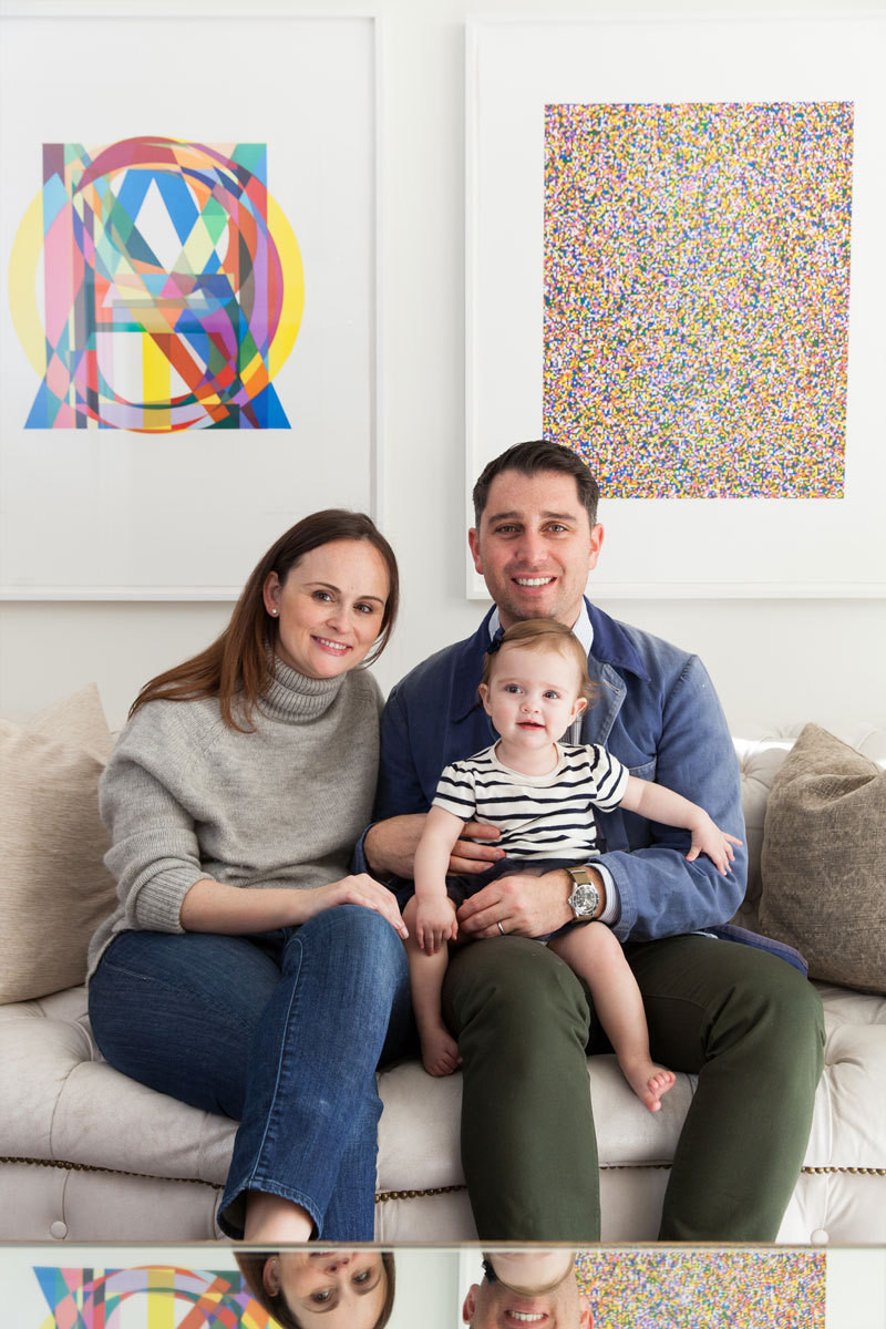 Jessica and Matt Farron, as well as 10-month-old daughter, Azie, pose in front of pieces from the couple's enviable art collection.
