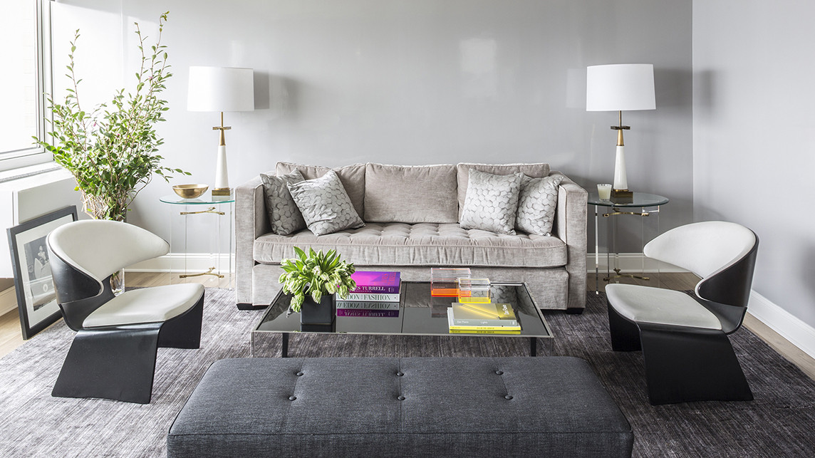 In the living room of a Manhattan home decorated by Sara Story, high-gloss gray walls and neutral furnishings foster a serene environment.