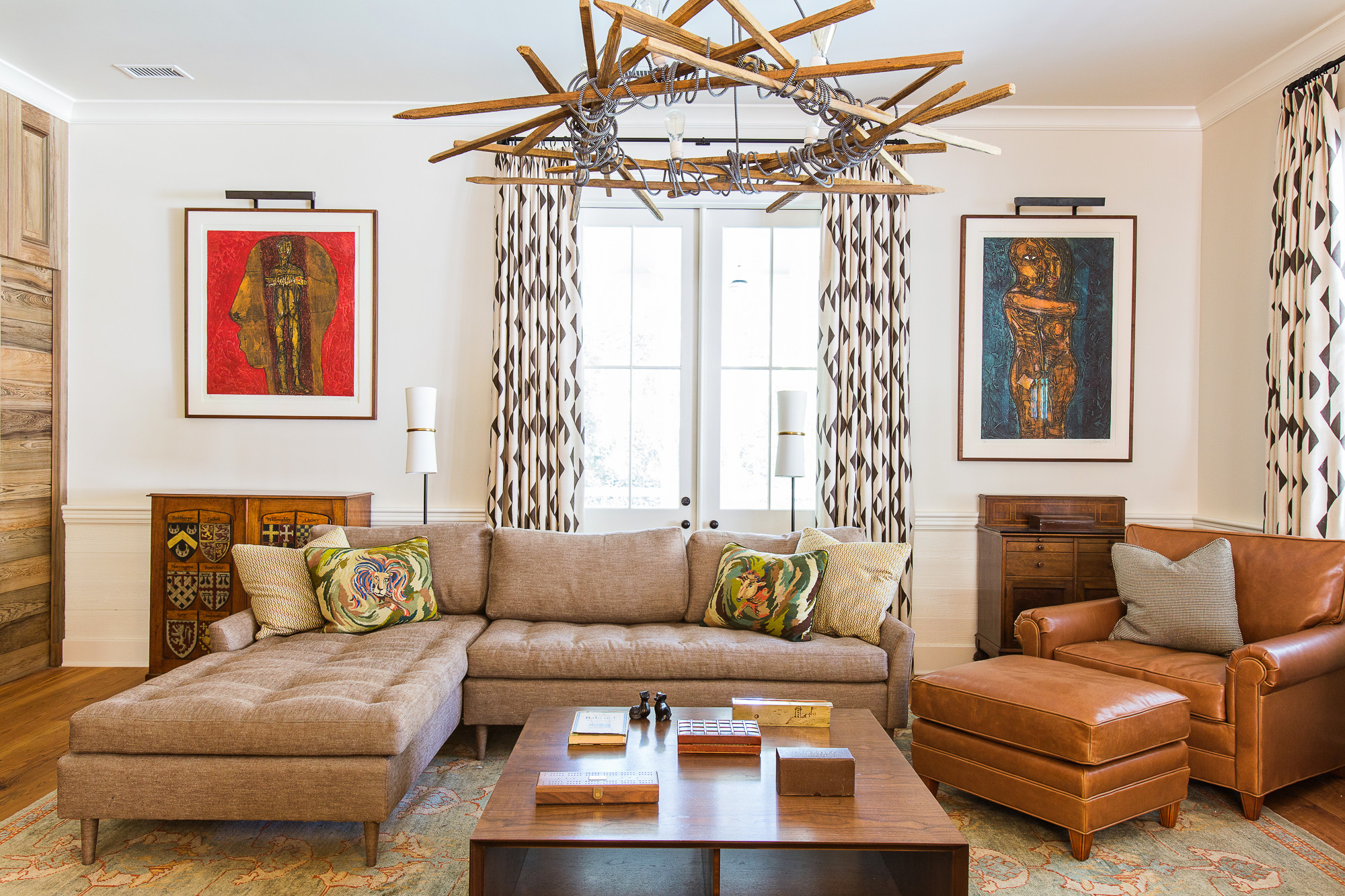 Interior designer Cortney Bishop created a warm and modern beach home by combining pieces that incorporated both refined masculinity and an homage to the past. In the family room, an Old Modern Objects tobacco stick chandelier holds center court to the traditional Ralph Lauren leather chair and ottoman and the Verellen leather sectional sofa below.