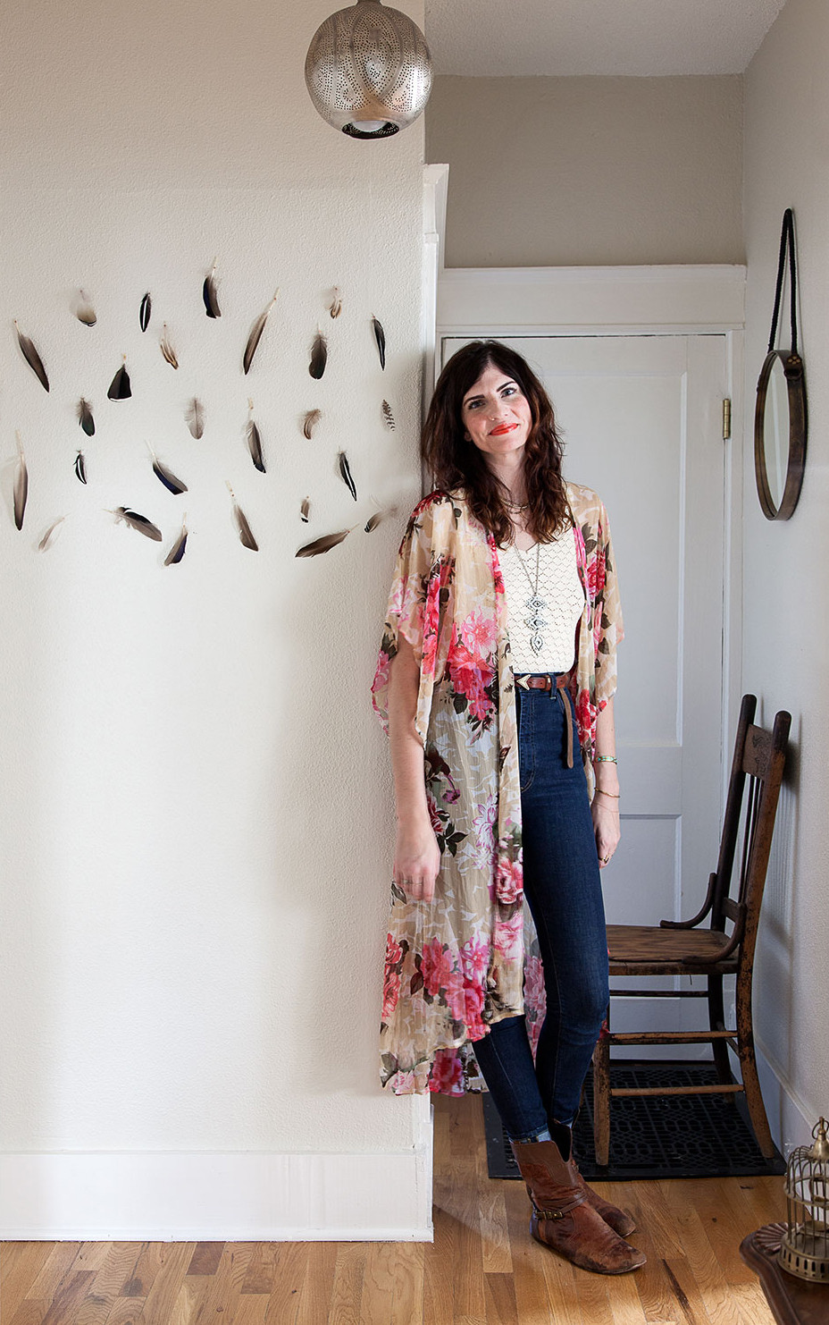 Stylist and designer Ruthie Lindsey next to a feather installation on her wall.