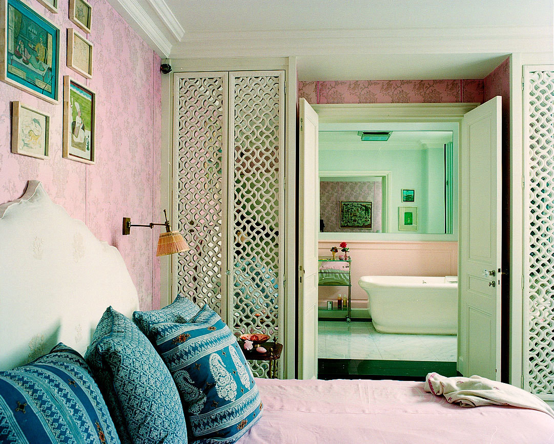 Pink walls encompass the bedroom, a small gathering of art hangs above an upholstered headboard.