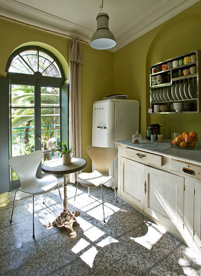 In the kitchen, intricate antique cement floor tiles play off simple green-almond walls.
