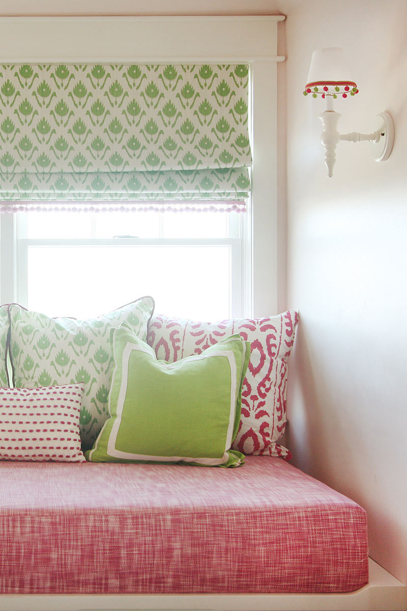 Pompoms and pillows embellish a cozy reading nook.